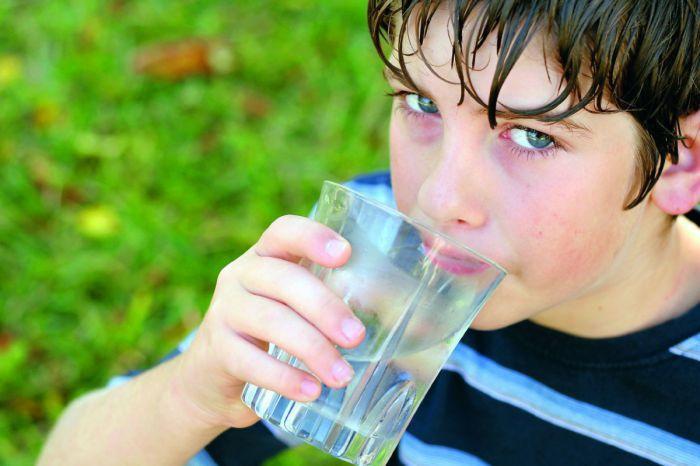 ein kleiner Bub trinkt Wasser aus einem Glas